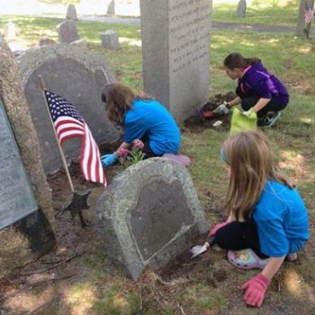 Kids from First Parish Plymouth cleaning Burial Hill